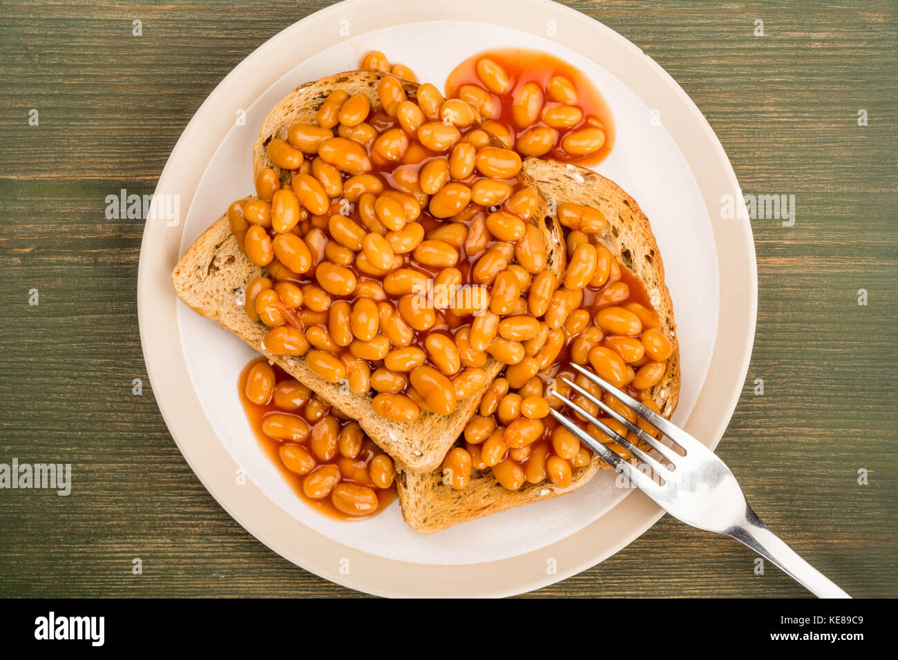 Baked Beans in Tomato Sauce on Toast On A Green Wooden Background - Stock Image