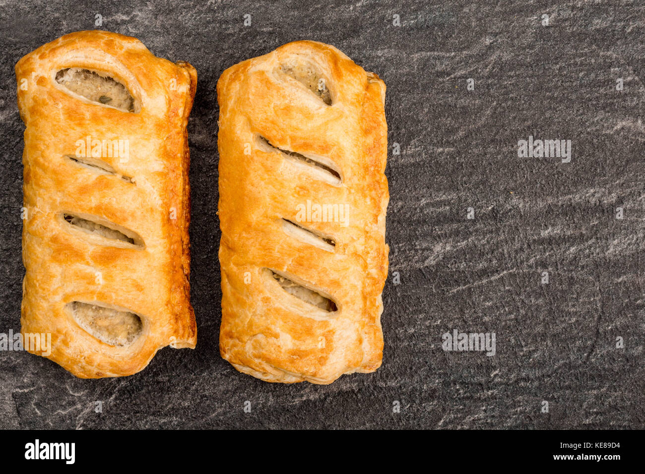 Sausage Rolls in Pastry On A Black Slate Kitchen Tile With Copy Space - Stock Image