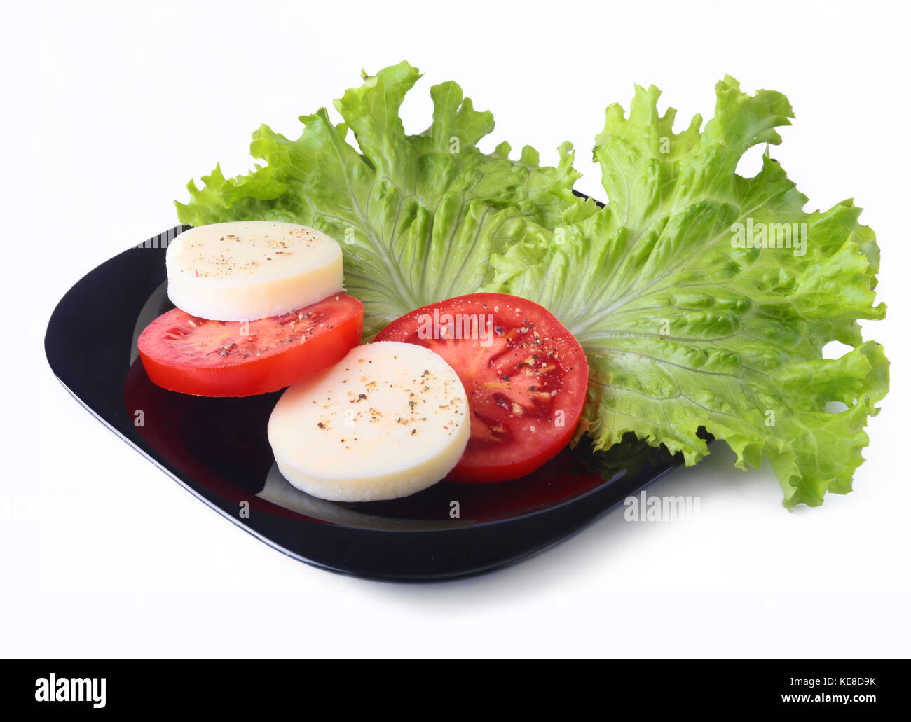 Portion of Mozzarella with Tomatoes, lettuce leaf and Balsamic dressing on black plate. selective focus close-up - Stock Image