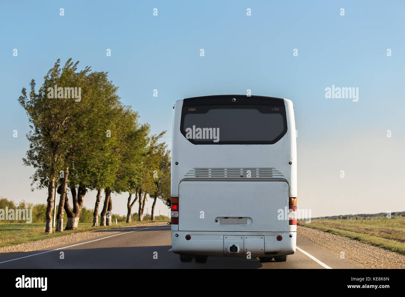 White intercity bus is driving along the road. Back view. Sunny day. The sky without clouds. - Stock Image