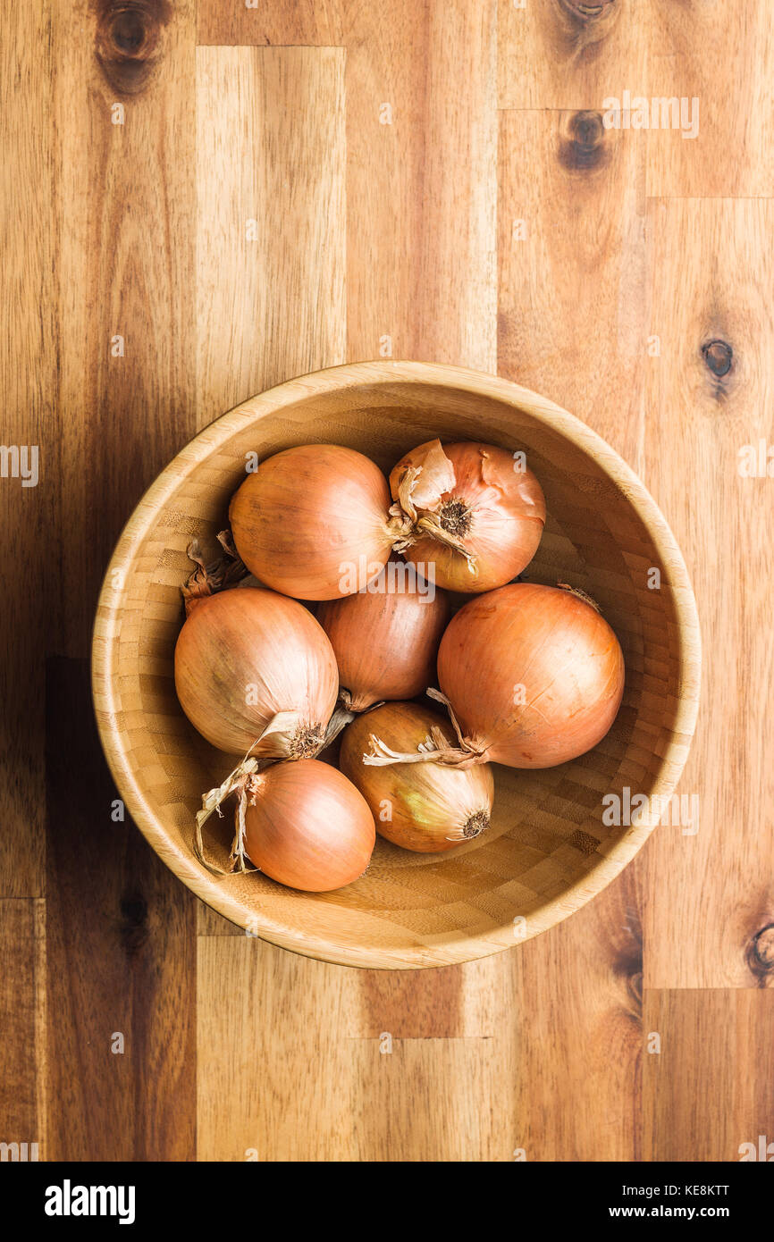 Fresh onion bulbs in wooden bowl. Stock Photo