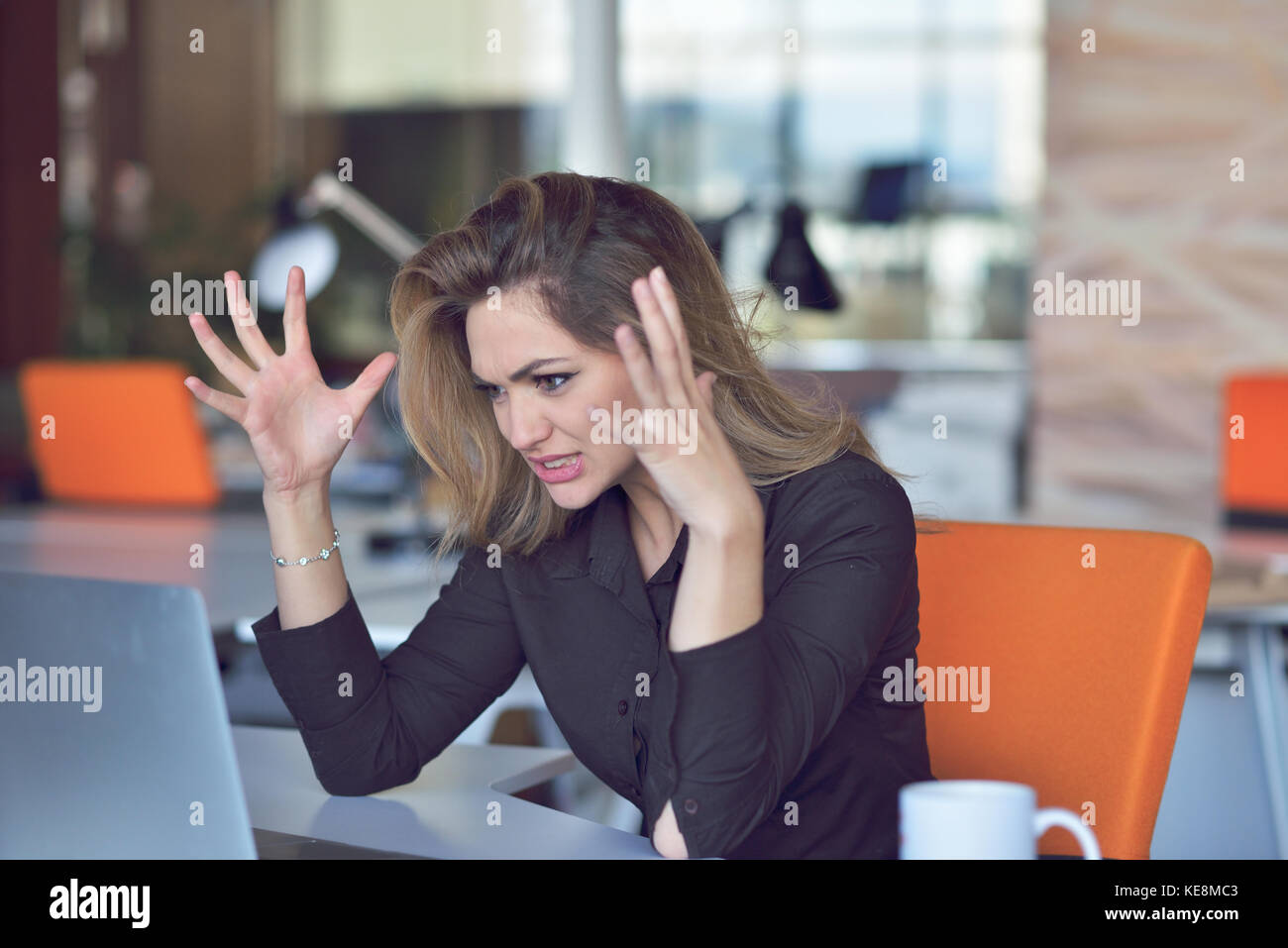 Frustrated angry woman screaming on her laptop. - Stock Image