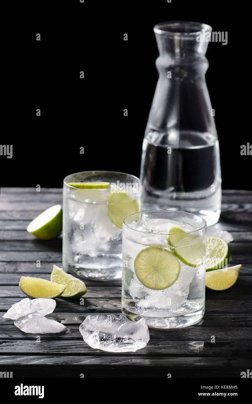 Selective focus composition with gin and tonic cocktail served with citrus on  wooden table with pieces of ice - Stock Image