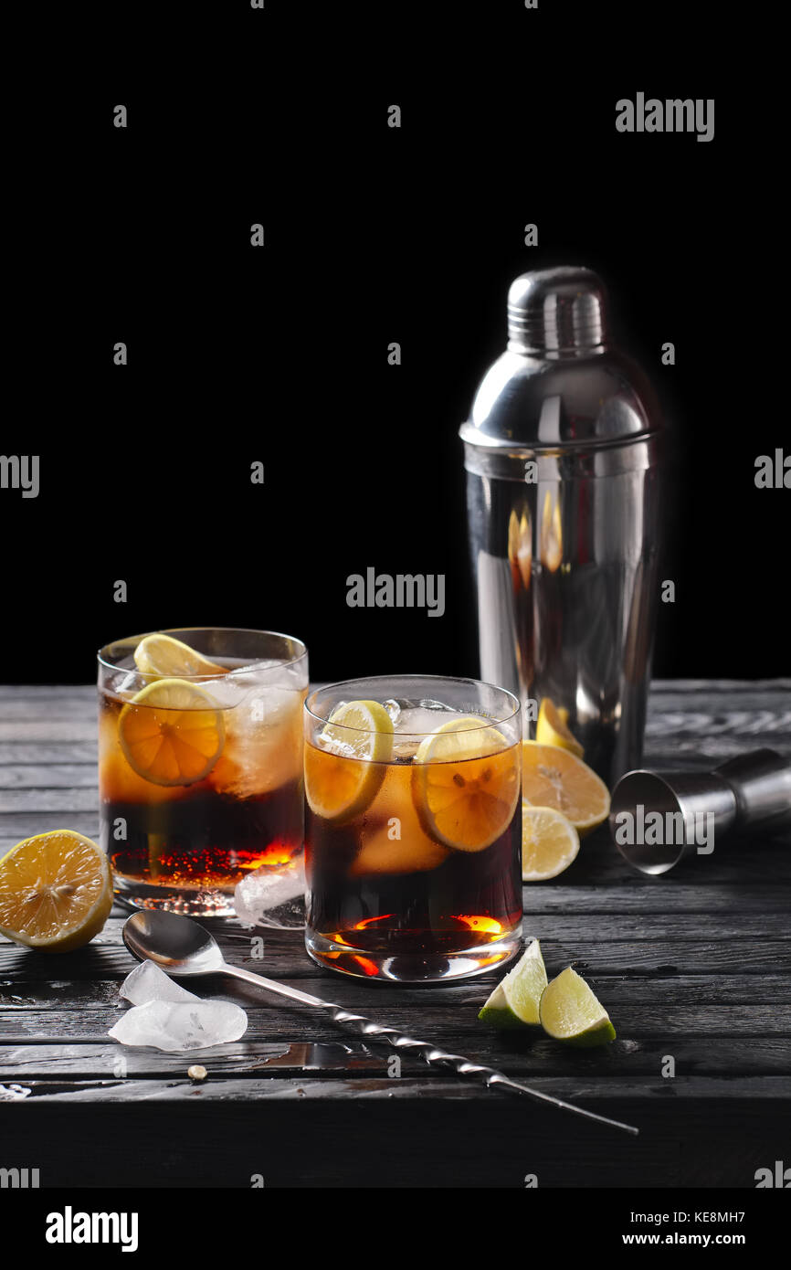 Selective focus composition with rum and cola cocktail served with  citrus on rough paper and fabrick over the wooden - Stock Image
