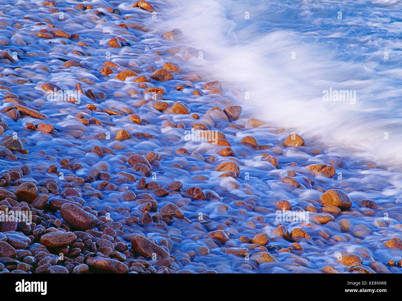 Channel Islands. Guernsey. Waves on pebble beach. - Stock Image