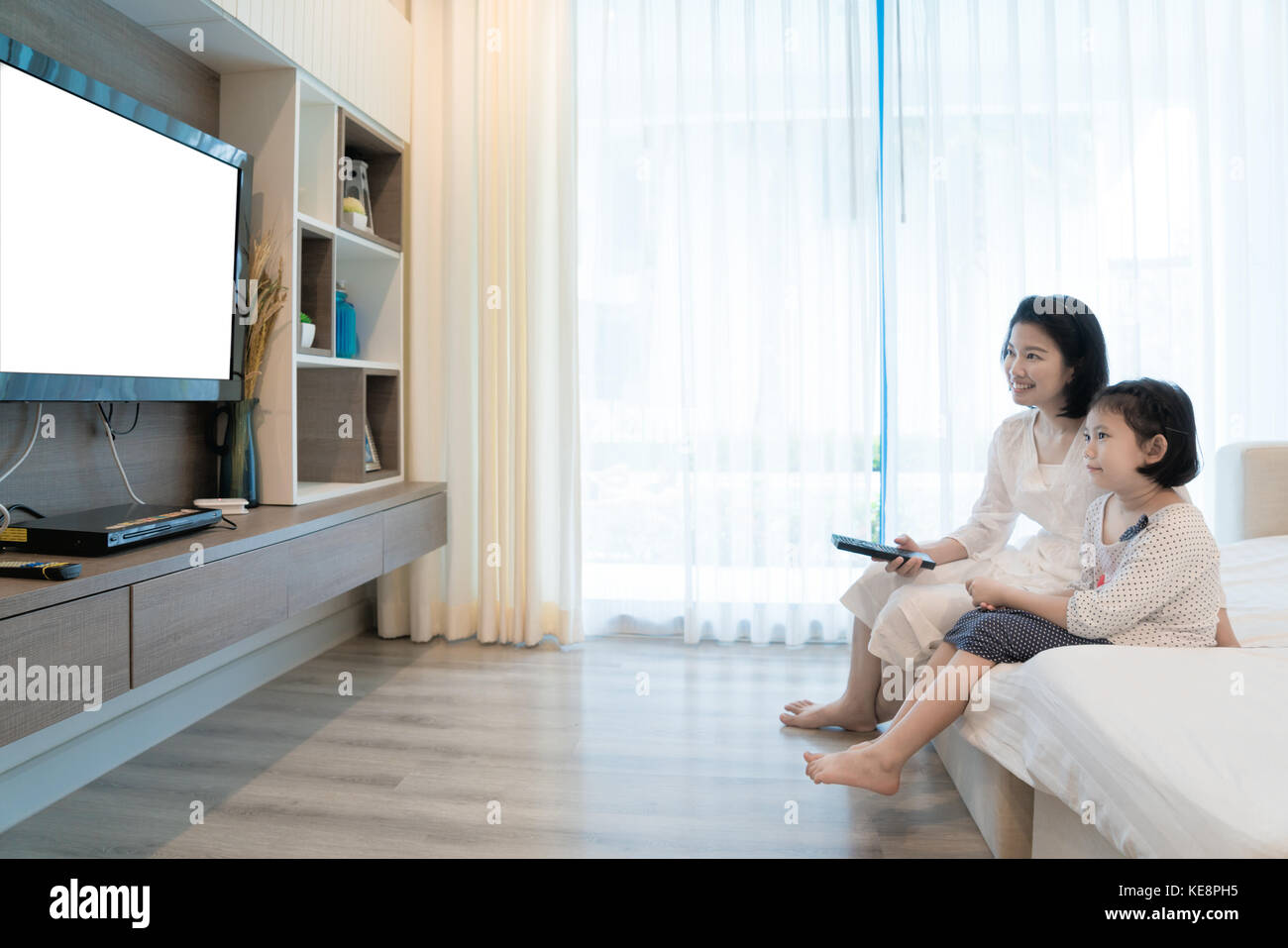 Happy Asian family mother and daughter sitting on sofa watching flat screen television at living room in home. Family - Stock Image