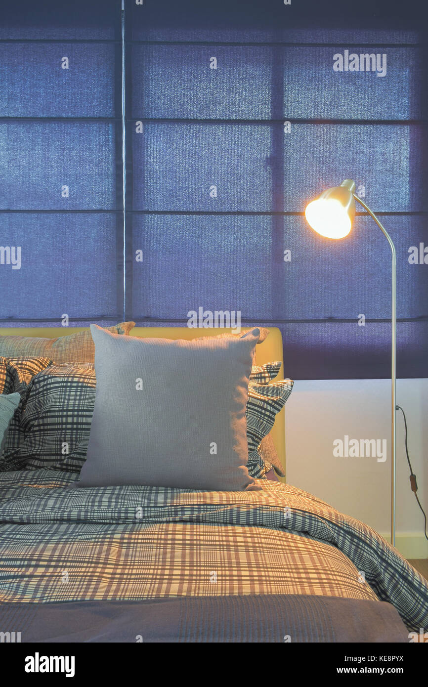 Floor lamp next to comfy bed in night time - Stock Image