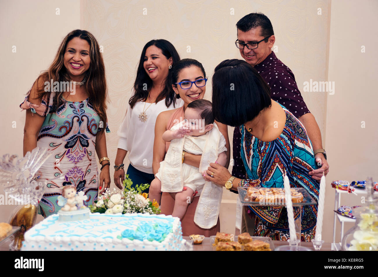 Guests having their picture taken with the just christened baby at his baptismal party Stock Photo