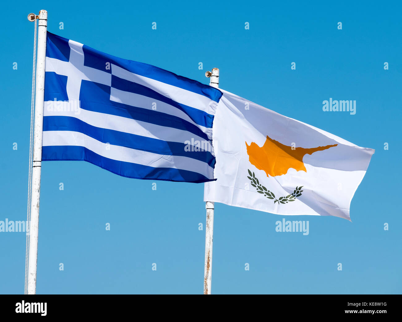 The flags of Greece and Cyprus flutter against a blue sky in Paphos Cyprus. - Stock Image