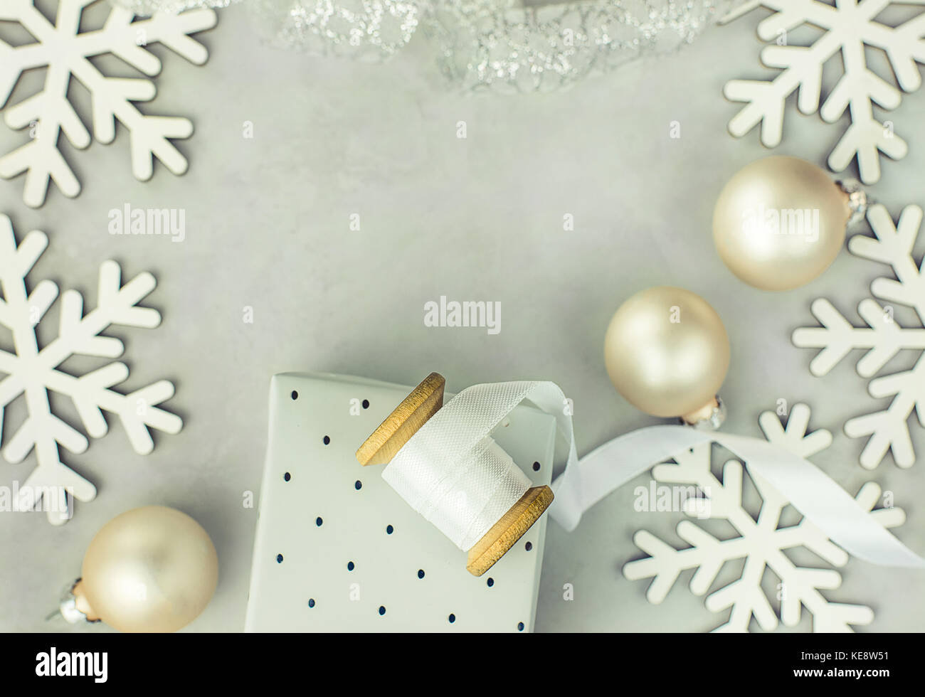 Gift boxes wrapped in silver paper. Wooden spool with white curled silk ribbon, Christmas baubles, snow flakes arranged - Stock Image