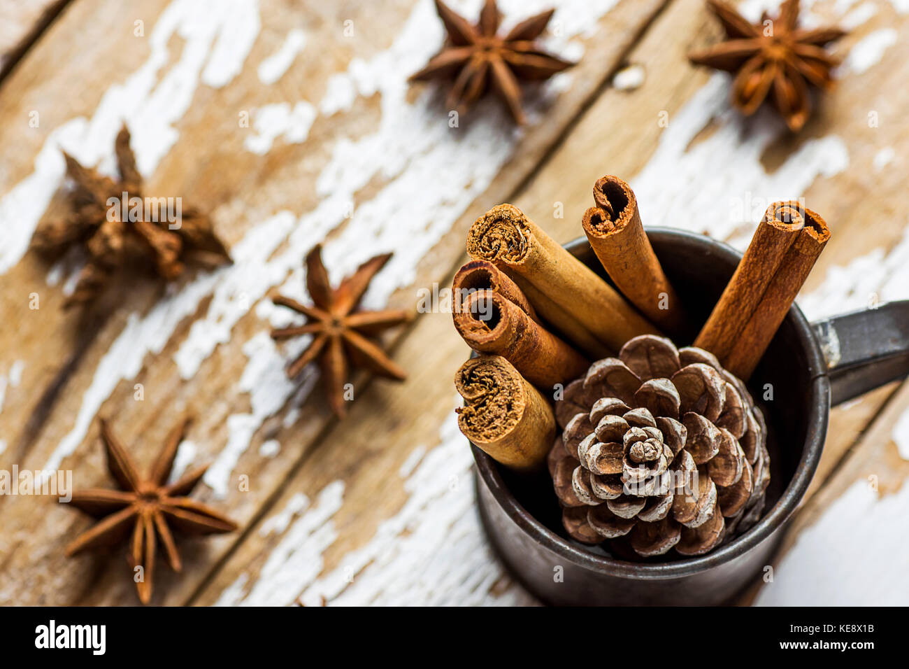 Christmas Baking Ingredients Decoration Cinnamon Sticks Scattered Anise Star Pine Cone in Vintage Jug on Snowy Wood - Stock Image