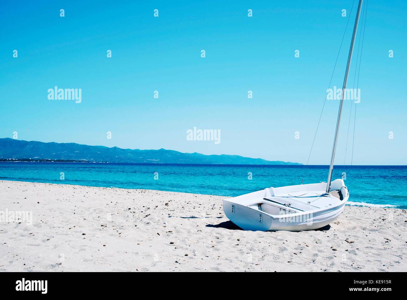 a sailboat stranded in the white sand of the Spiaggia del Poetto beach in Cagliari, Sardinia, Italy - Stock Image