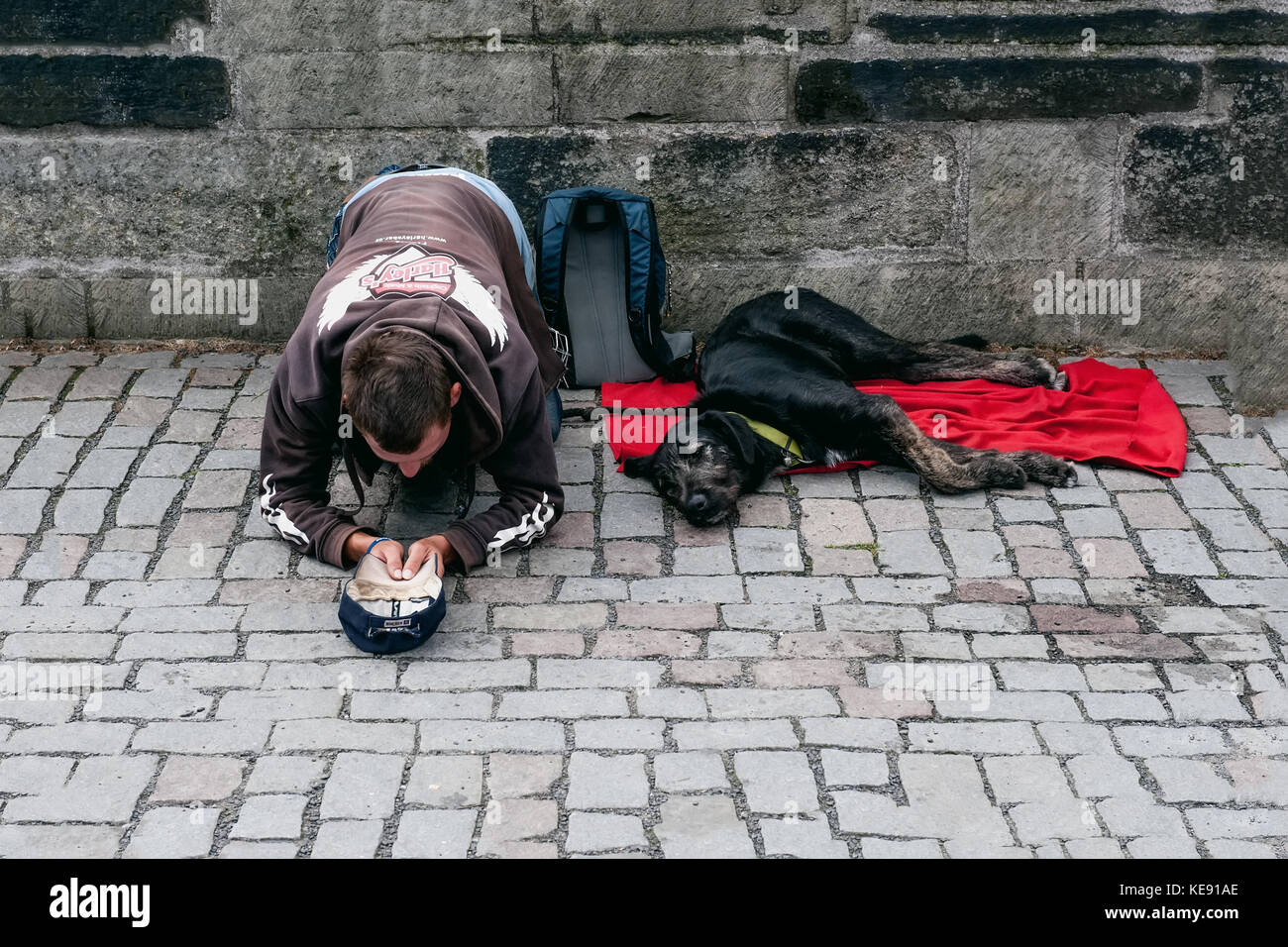 Prague 13.08.2013. A homeless young man with a big black dog on the street asking passersby for money. The horizontal - Stock Image