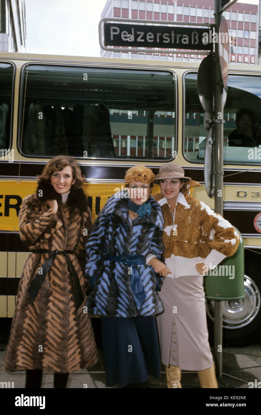 Three women are wearing fur coats in front of a bus in