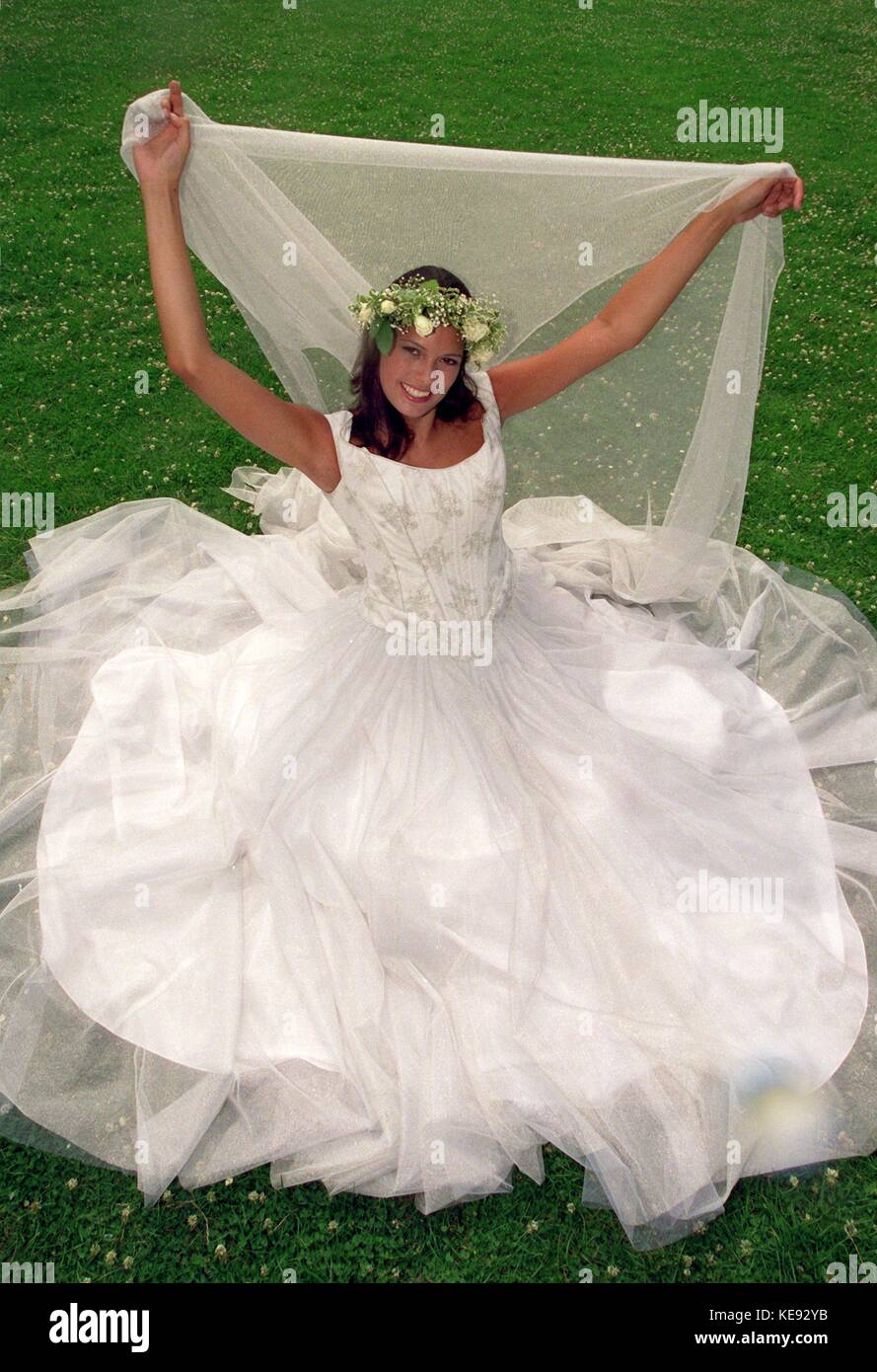 A classic wedding dress in white with several layers and a flower ...