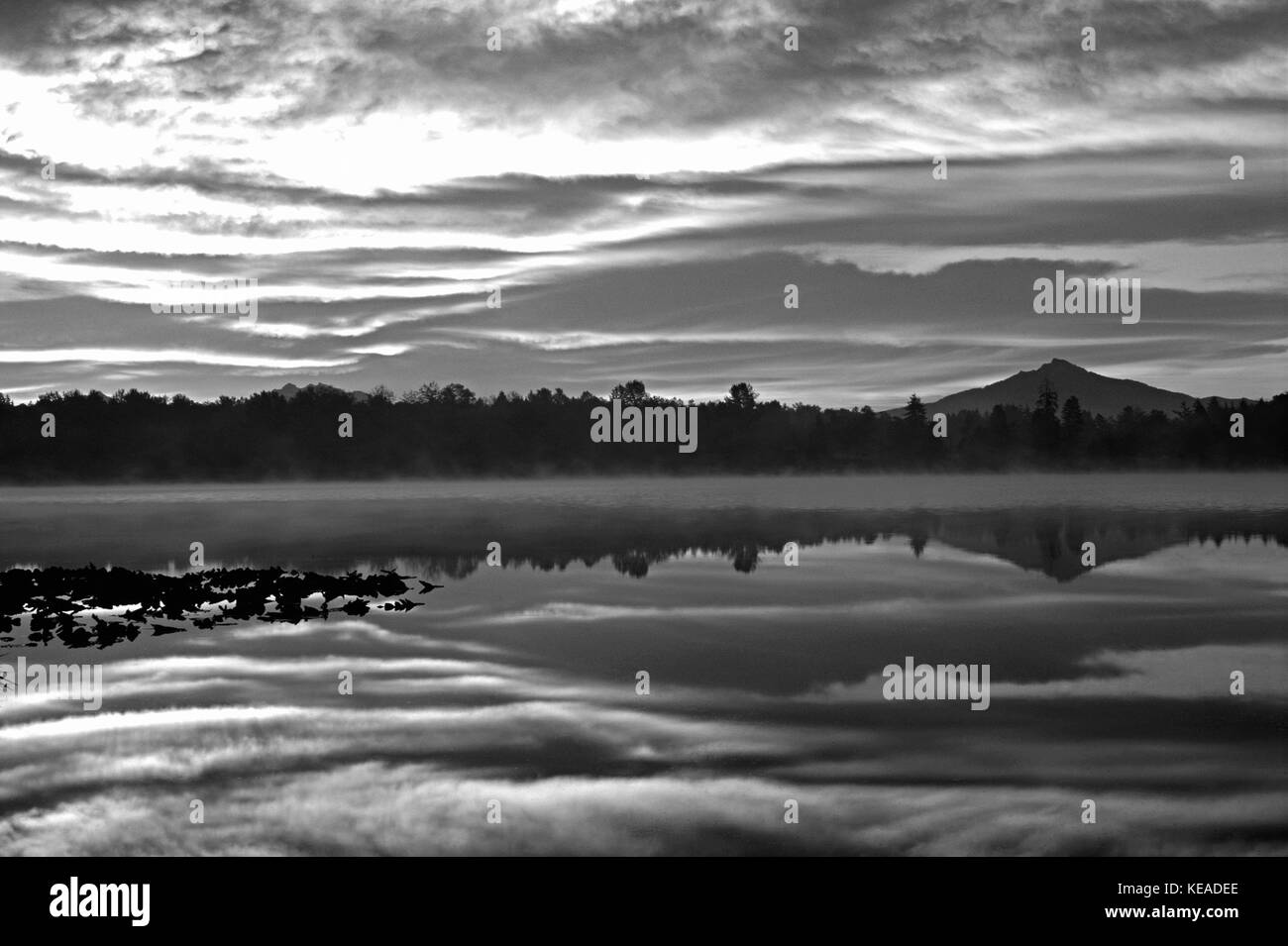 Dramatic sunrise over Lake Cassidy with Mount Pilchuck reflecting in calm lake early morning light, Snohomish County, - Stock Image