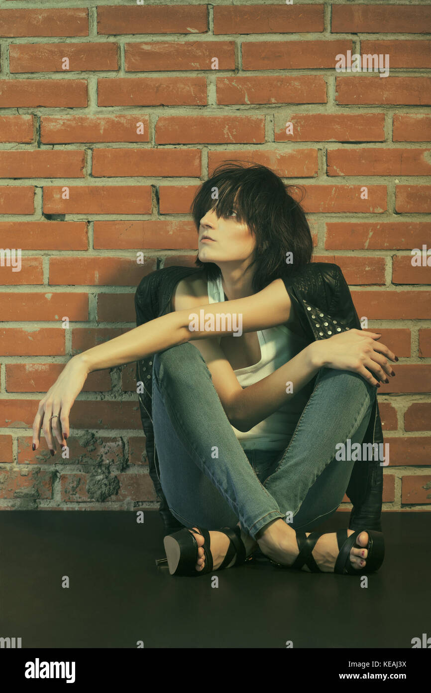 Androgyny female model in Heroin chic style near brick wall. Old style tinted image - Stock Image