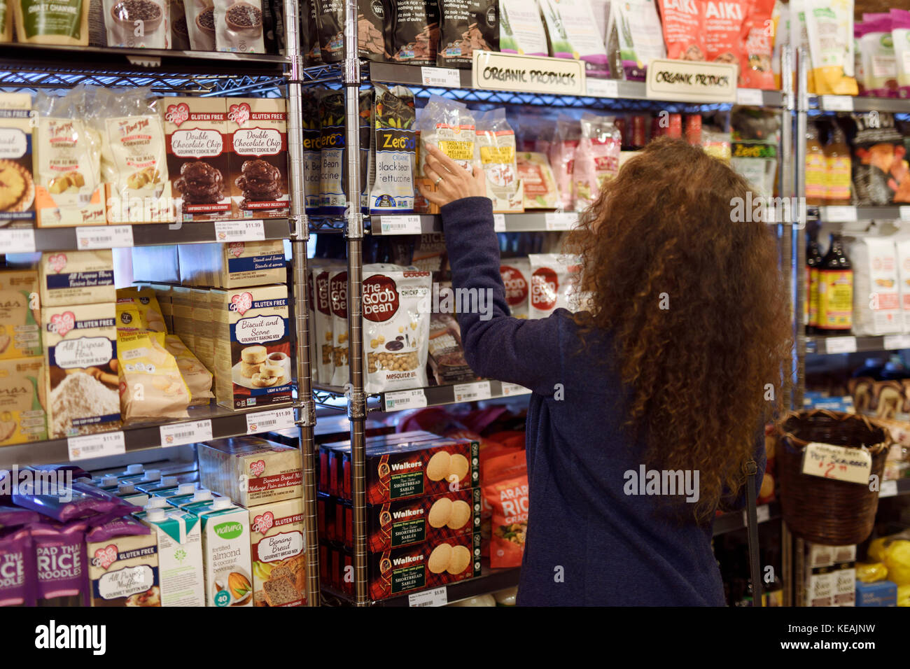 b97bb14bb71 Woman at a grocery store in organic products section Canada Stock ...