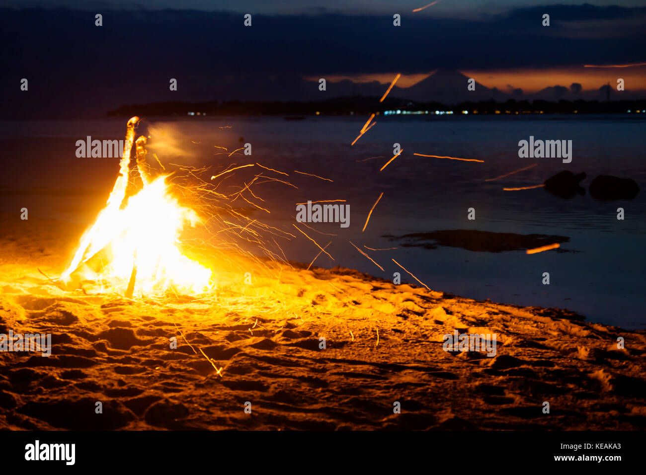 Bonfire at the beach of Gili Air with flying sparks and volcano Agung of Bali in the background - Stock Image