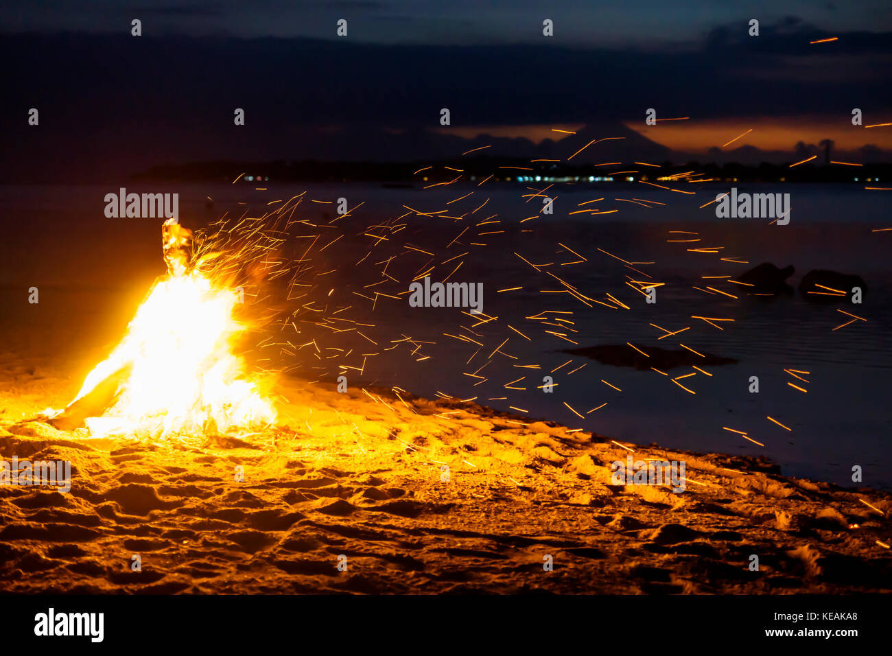 Fyling sparks from bonfire at the beach of Gili Air with volcano Agung of Bali in the background - Stock Image