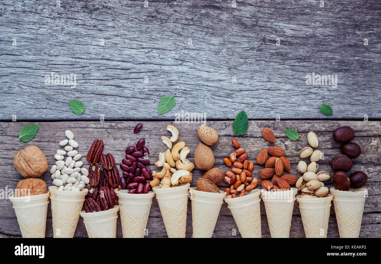 Concept for homemade various nuts ice cream. Mixed nuts in waffle cones on shabby wooden background.top view - Stock Image