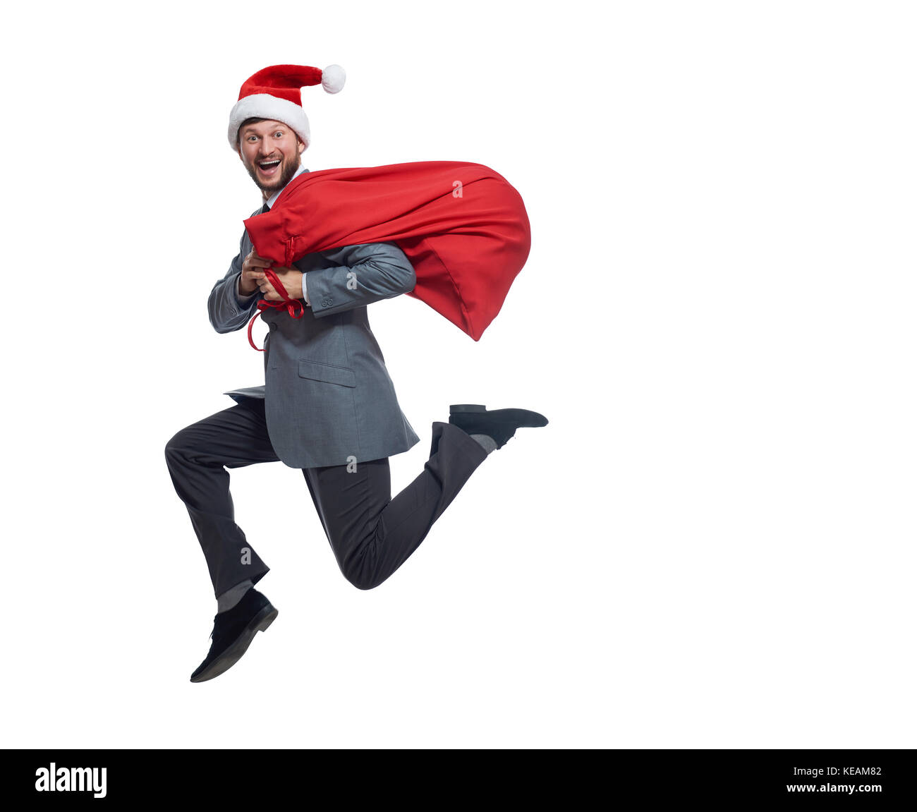 Happy santa clause jumping with bag of presents and gifts. - Stock Image