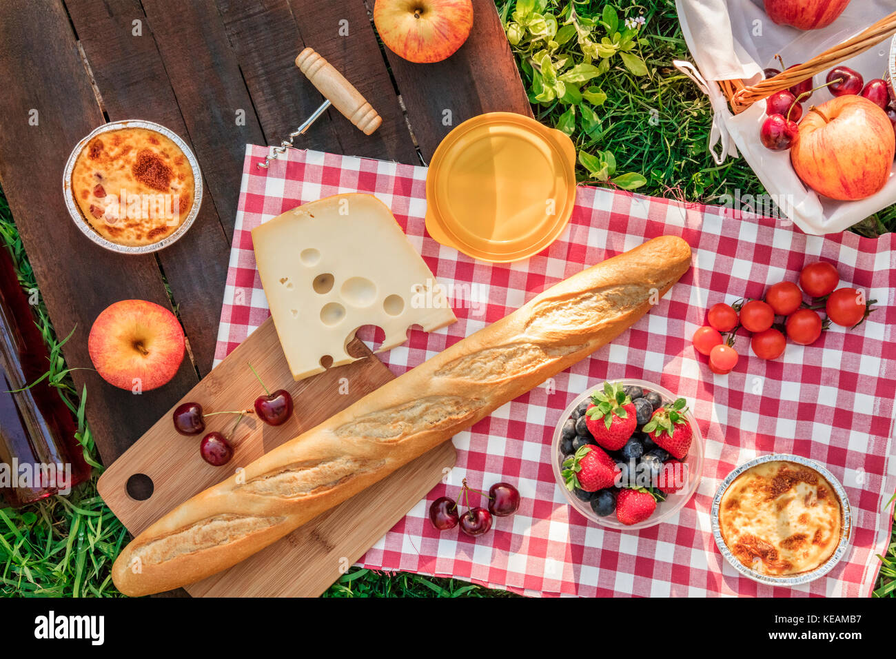 An overhead photo of a picnic with an apple, a bottle of rose wine, fresh cherries, a quiche, a corkscrew, and a - Stock Image