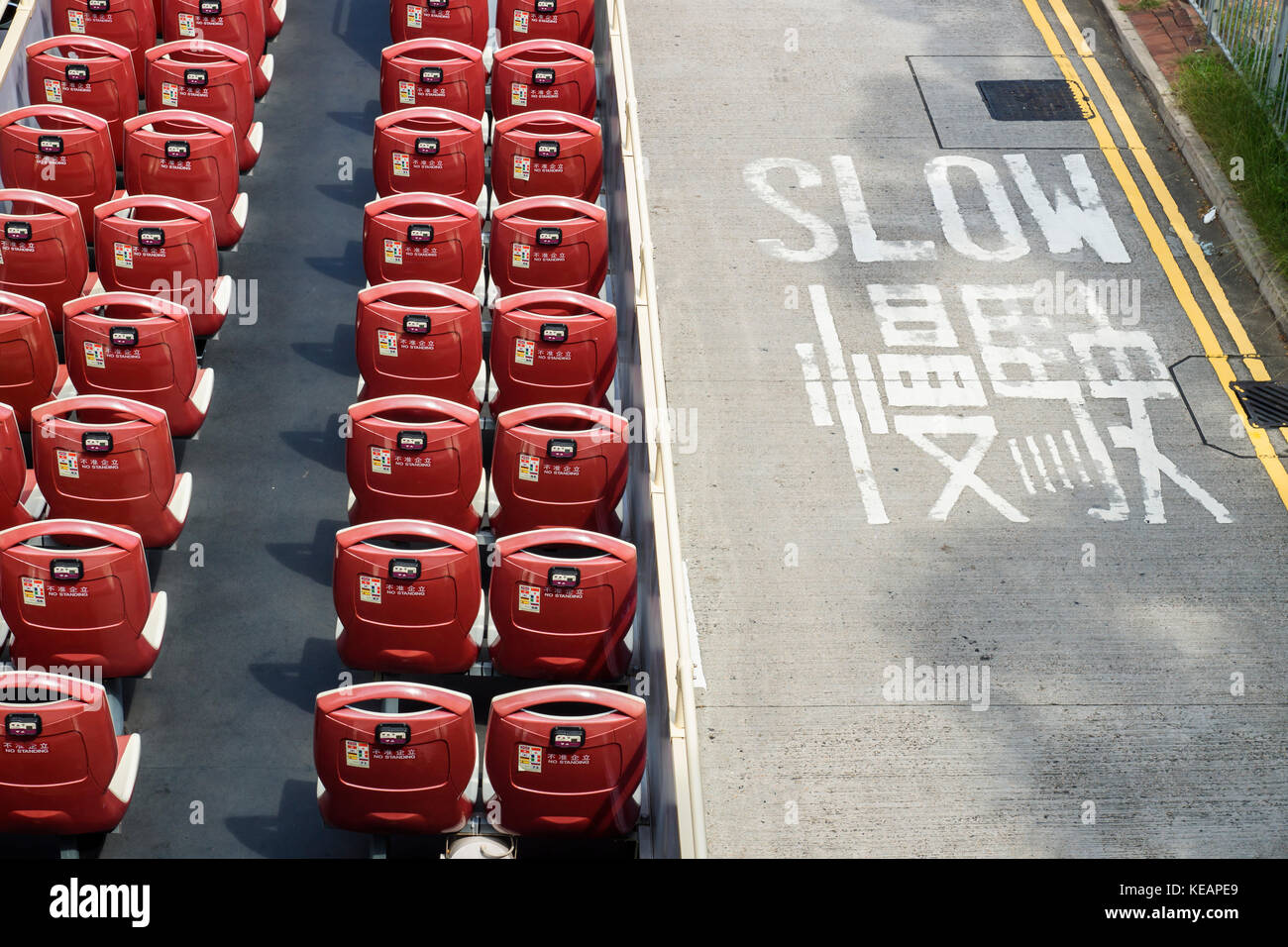 Open double decker bus with red chairs from high angle view with roadsign slow, Hong Kong, Asia - Stock Image