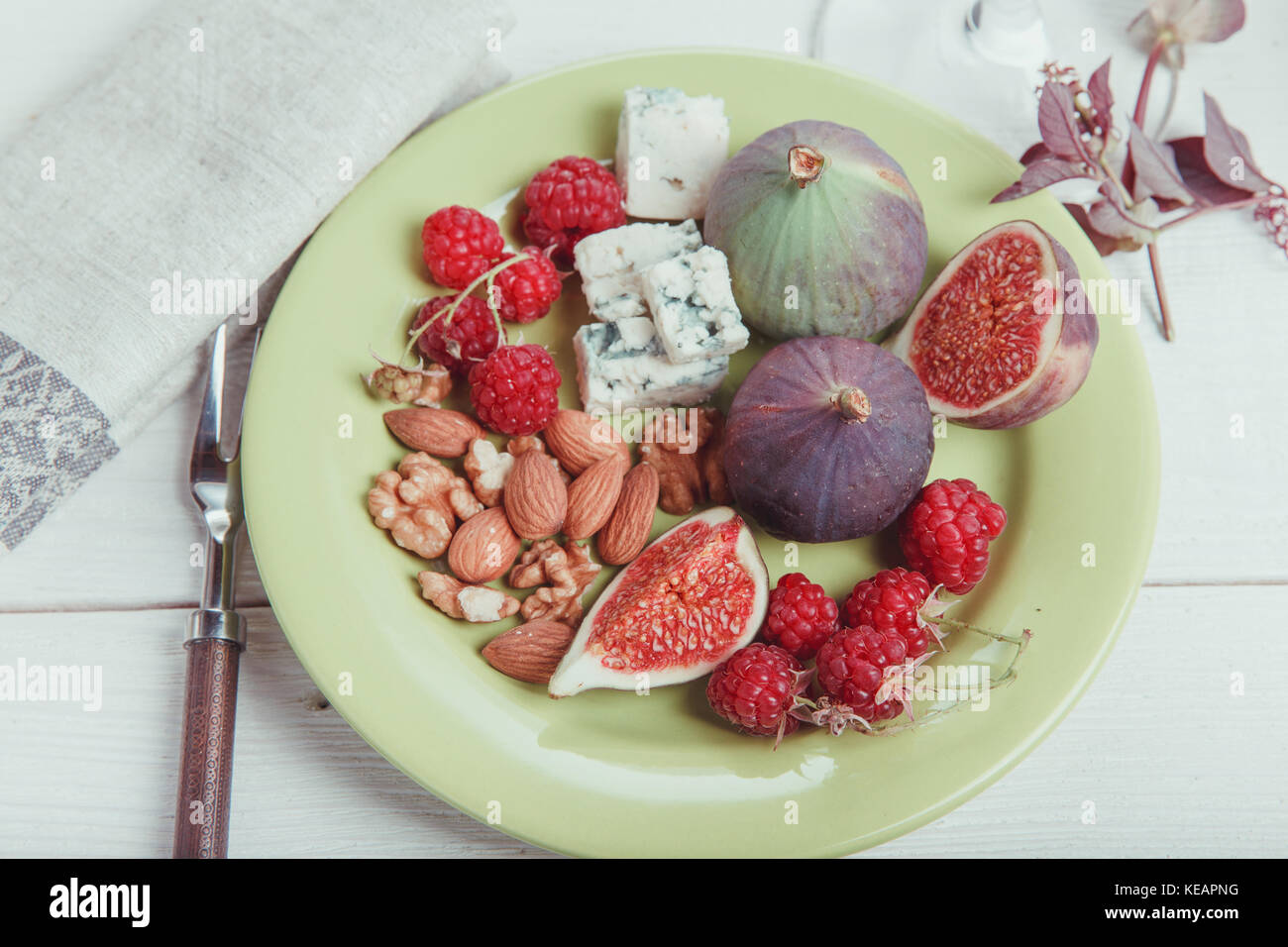 Serving the table, fresh figs, fruits, berries, cheese, nuts on a white wooden background - Stock Image
