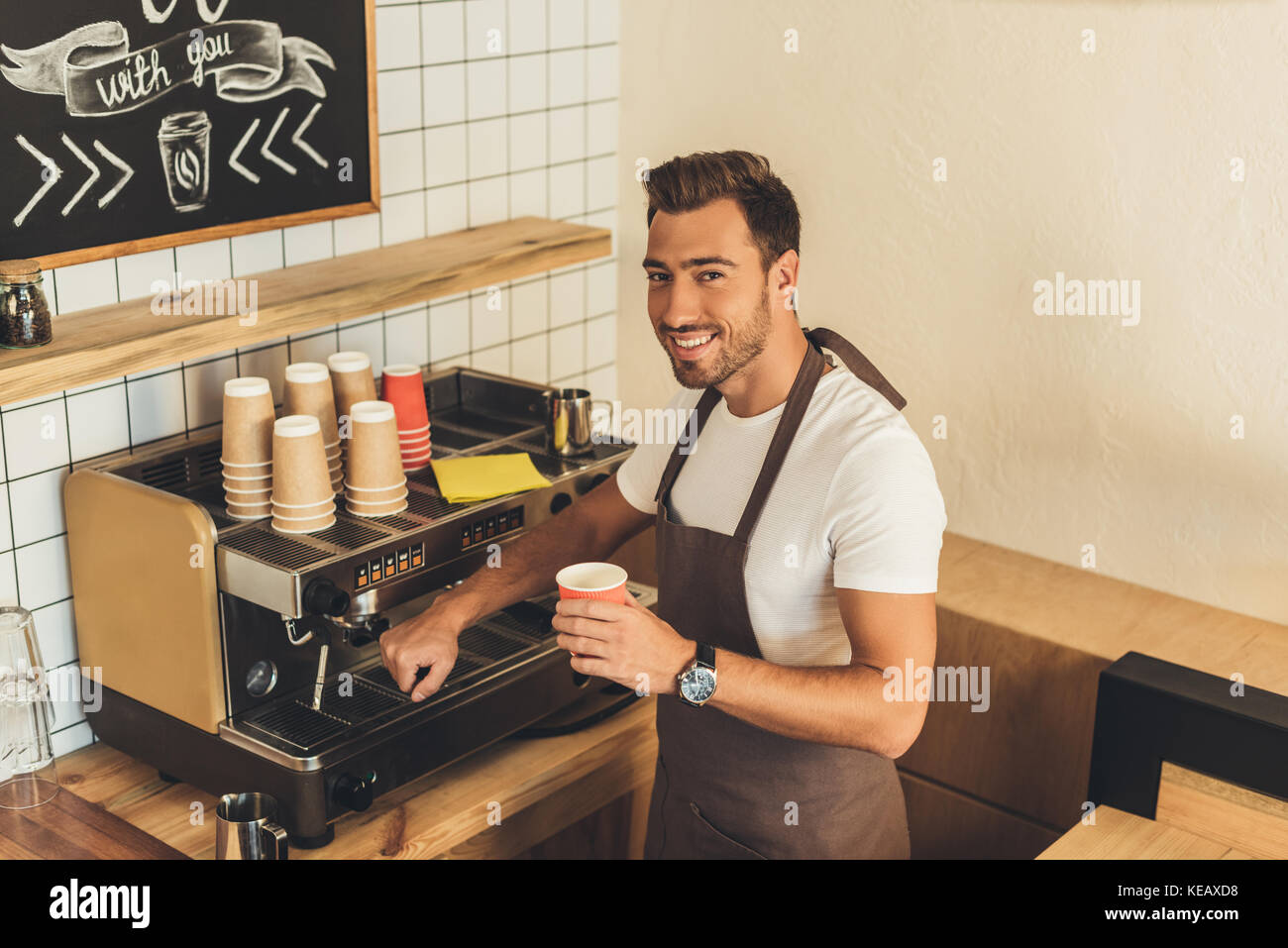 smiling barista with coffee to go - Stock Image