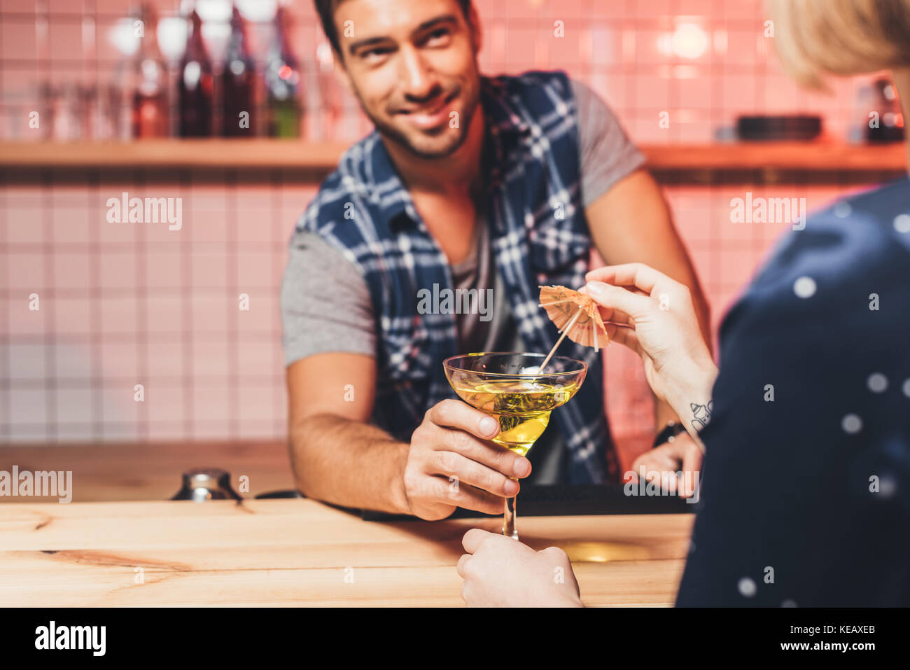 barman giving cocktail to visitor - Stock Image
