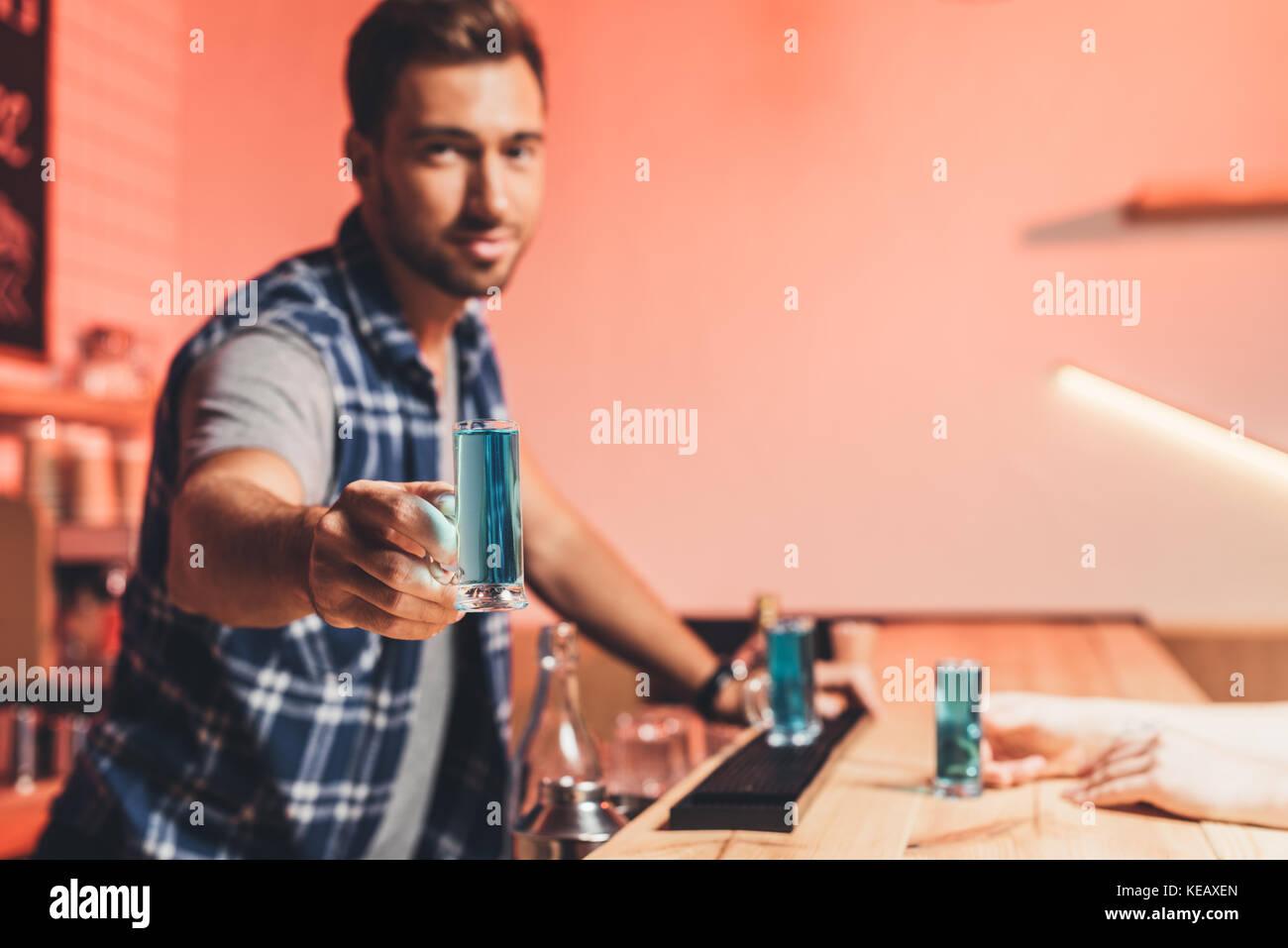 barman holding alcohol shot - Stock Image