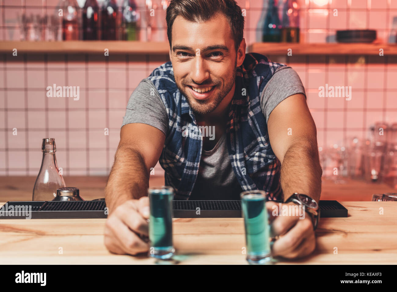 barman with alcohol shots on counter - Stock Image