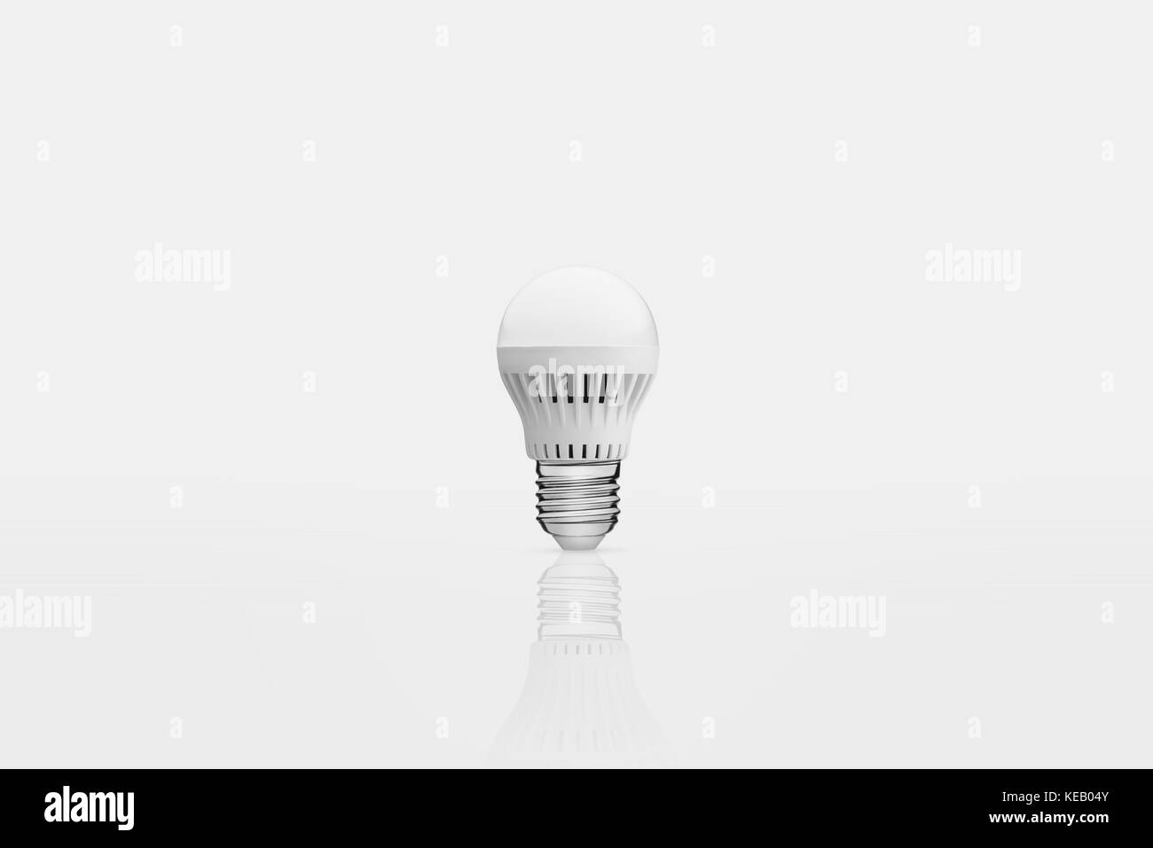 one energy saving lamp on a white background with reflection - Stock Image