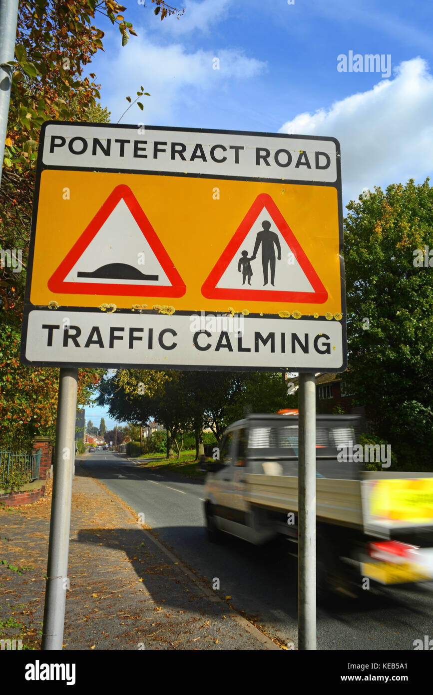truck passing traffic calming zone warning sign of speed bumps and pedestrians in road ahead on pontefract road - Stock Image