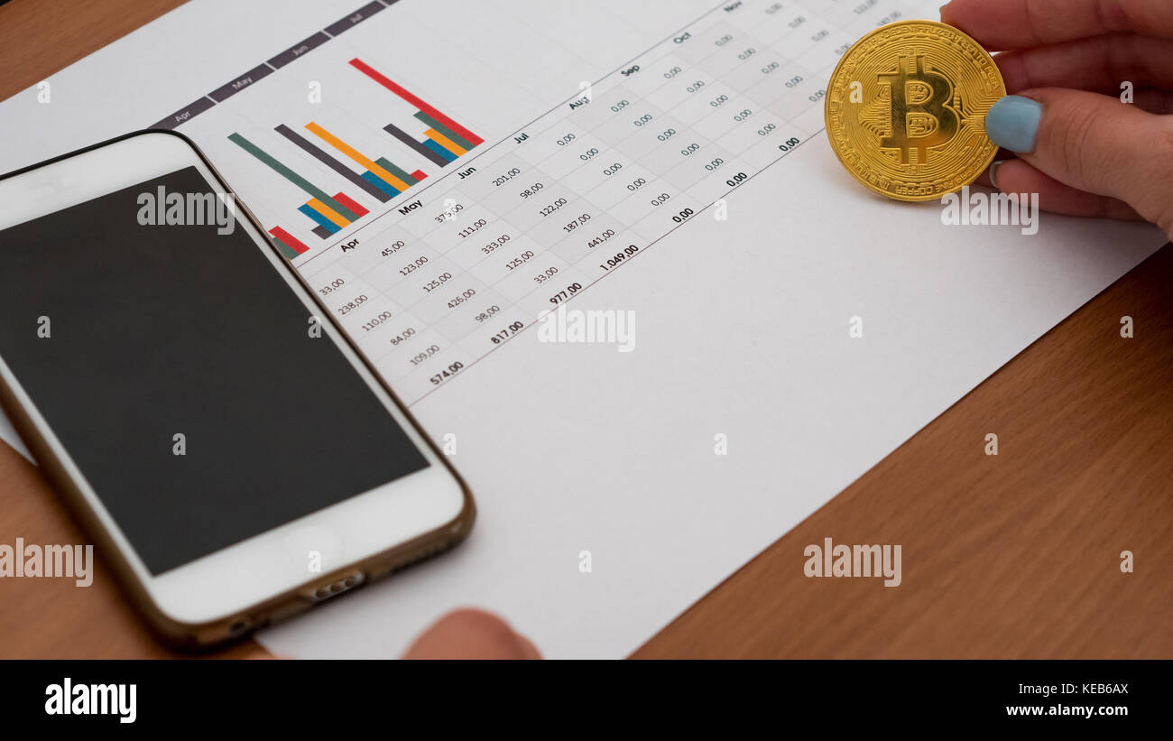 Woman holding bitcoin over finance statements in office top view - Stock Image