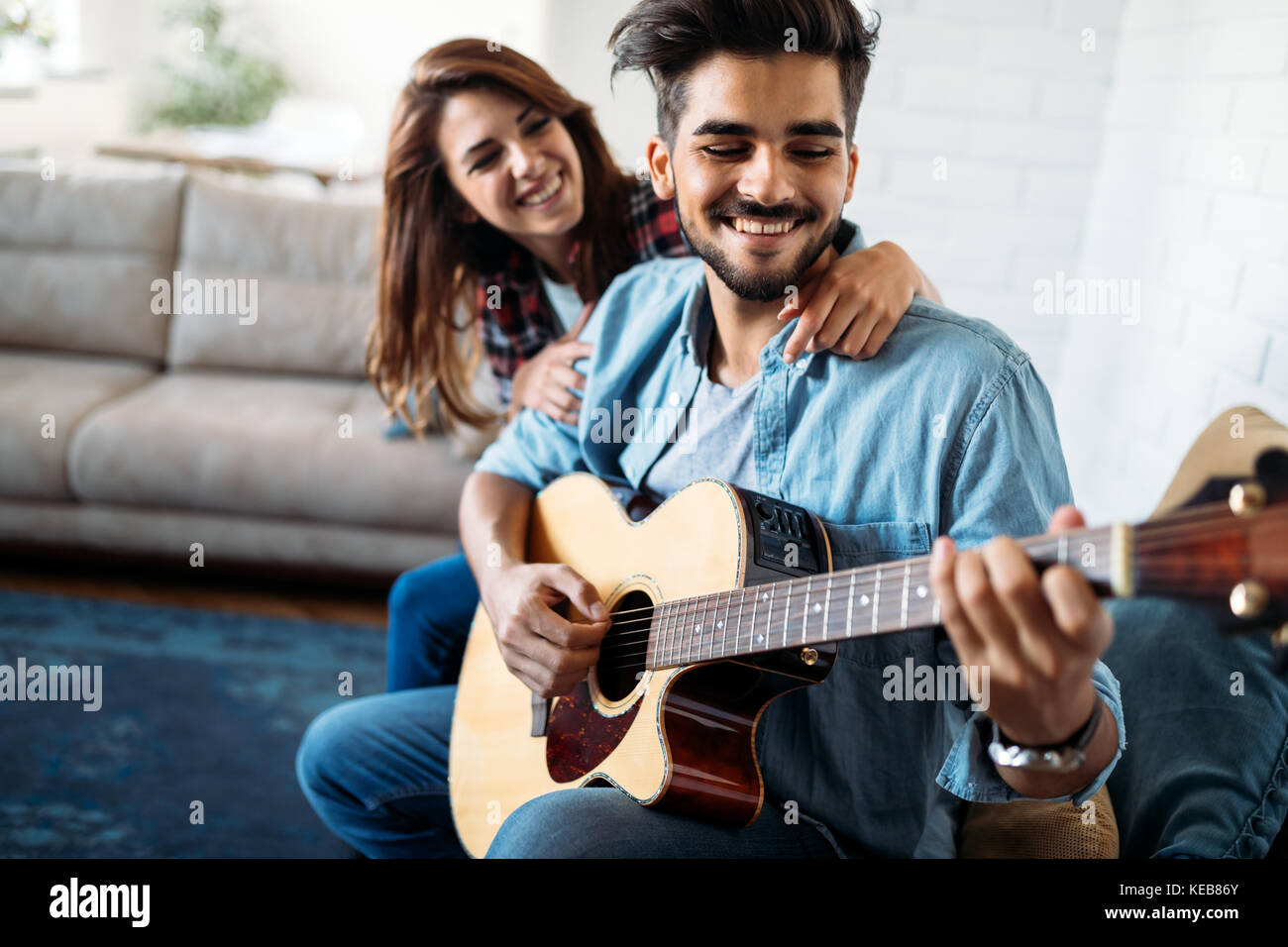Young handsome man playing guitar for his girlfriend - Stock Image