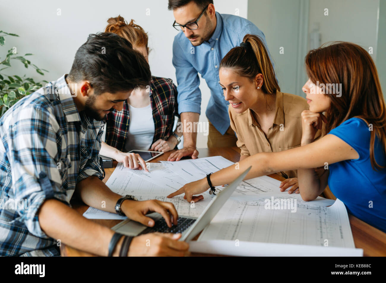 Image of business partners discussing documents and ideas - Stock Image