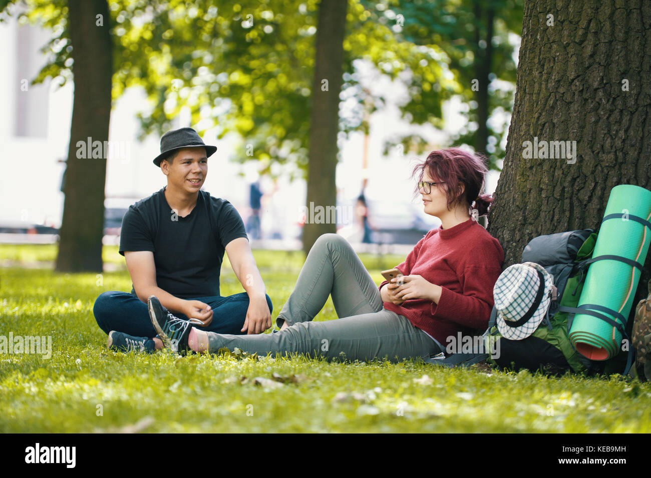 Couple of teenagers tourists with backpacks have rest in the city park near big tree - Stock Image