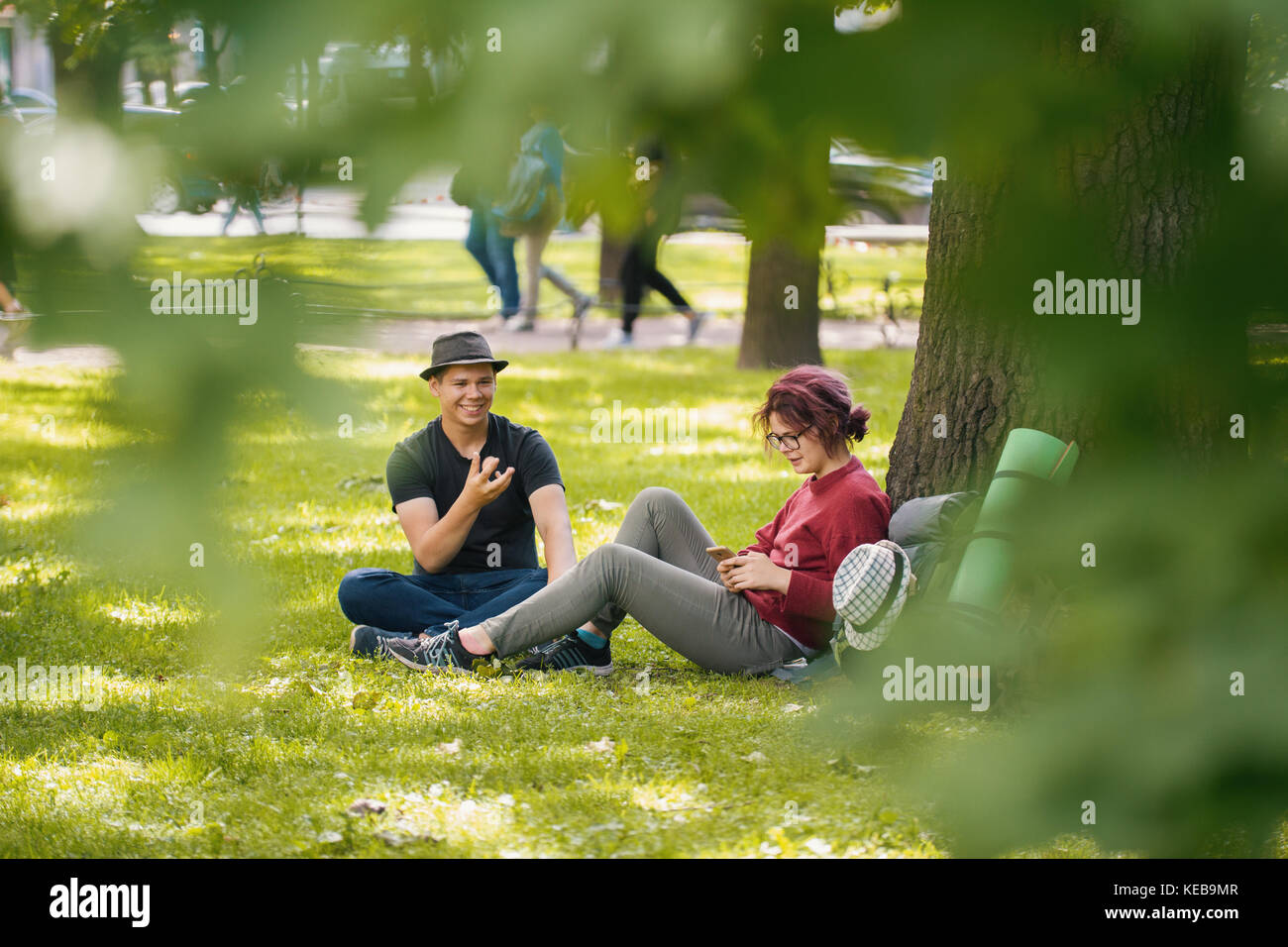 Young man and woman tourists with backpacks have rest in the park - Stock Image