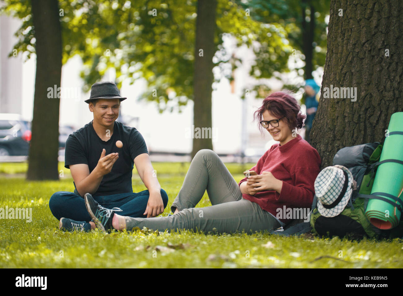 Young students - boy and girl with backpacks after hiking have a rest in the park - Stock Image