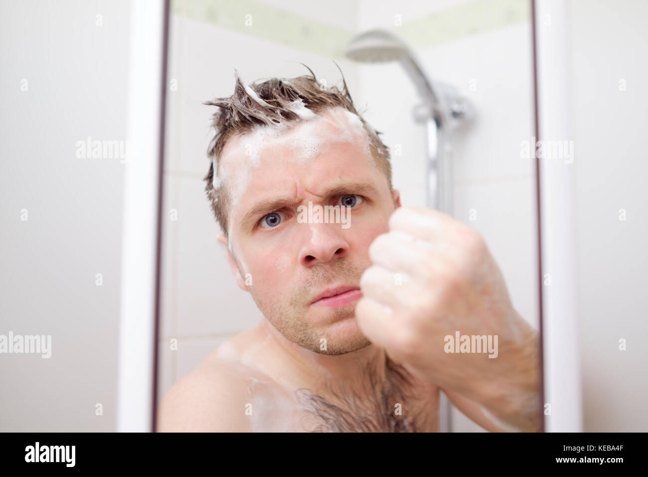 An angry man is showing a fist. He takes a shower and tries to protect his private space. - Stock Image