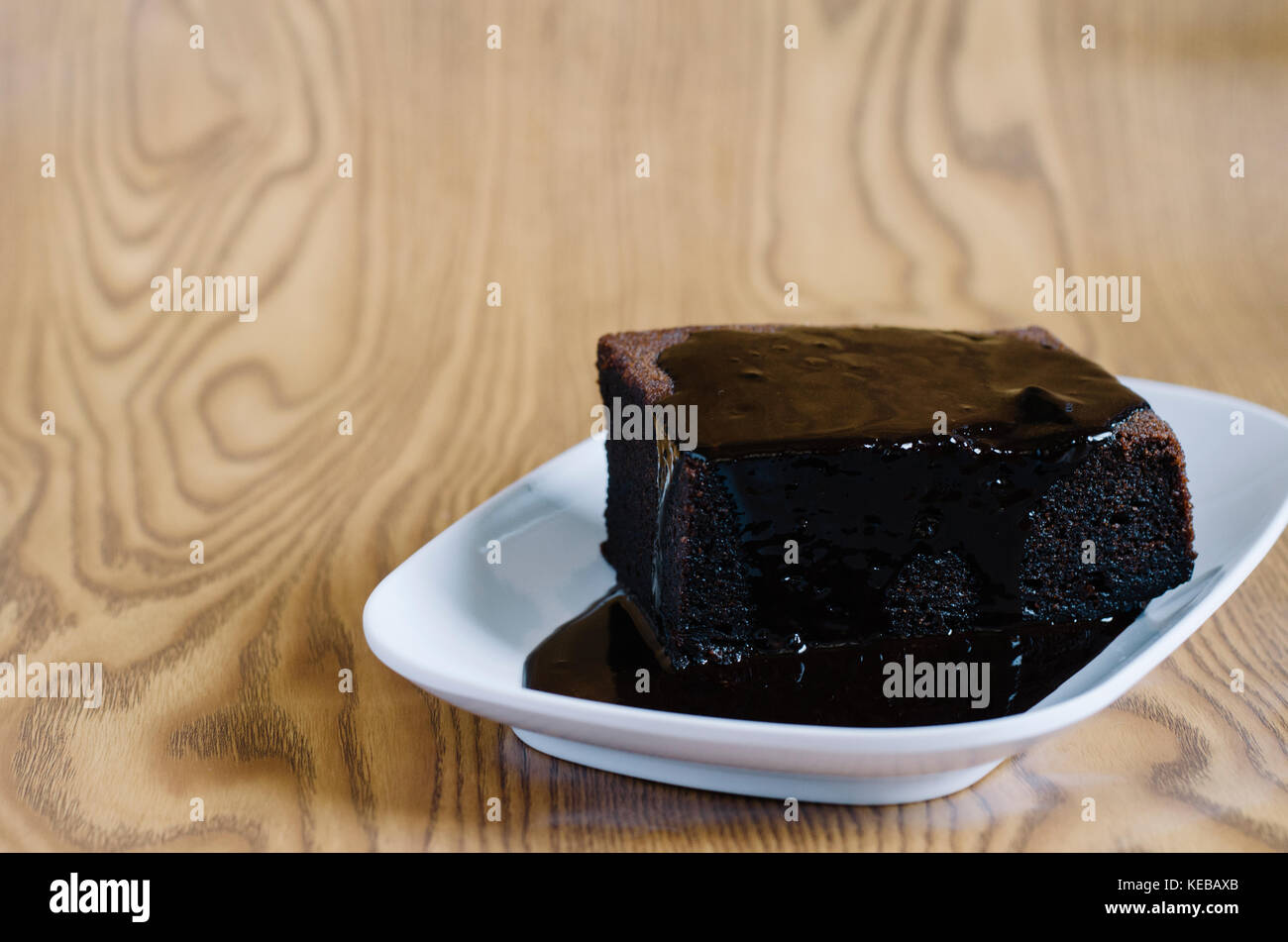 Chocolate sponge cake covered with melted chocolate. - Stock Image