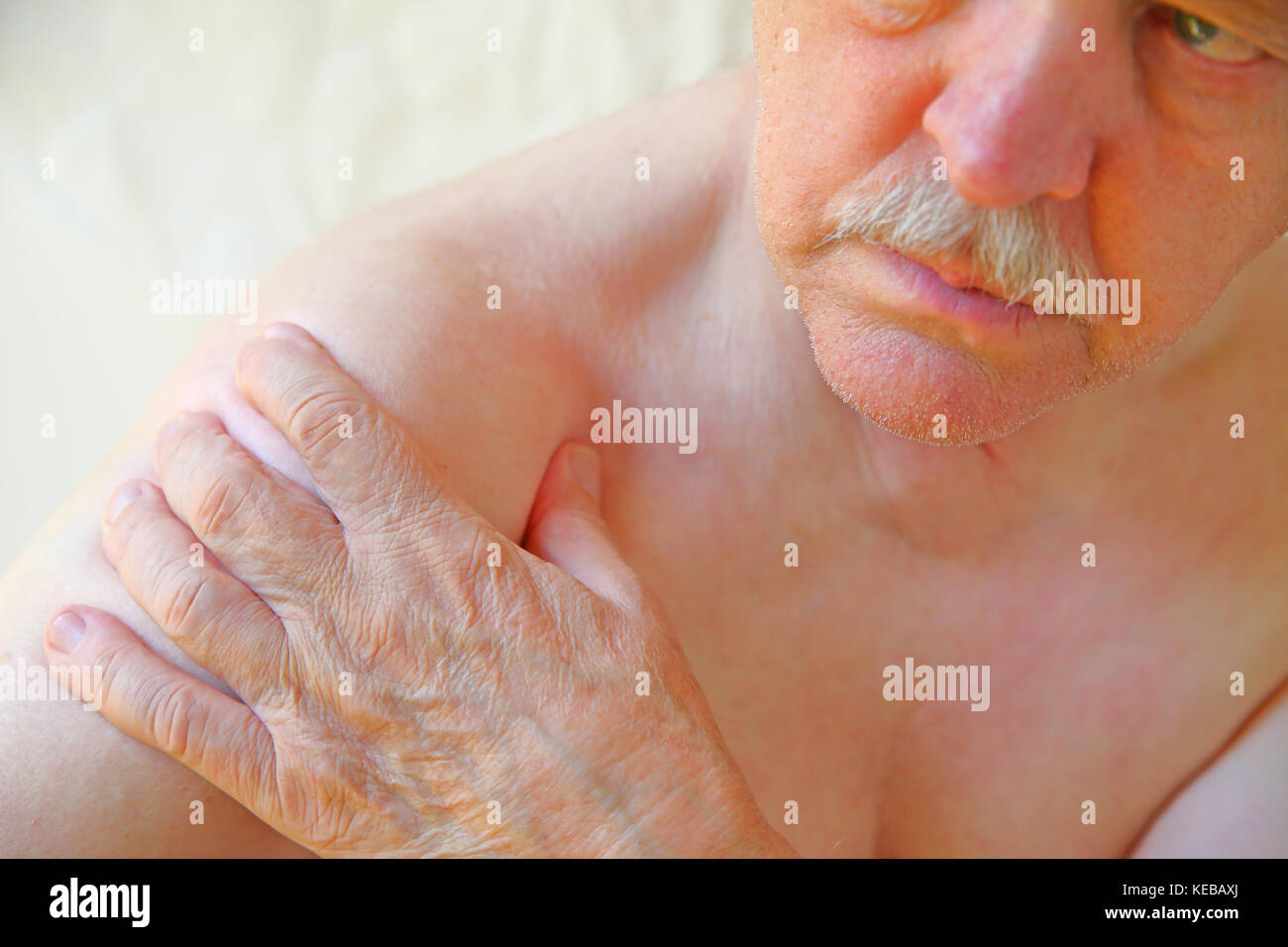 An older man with a hand on an aching shoulder joint - Stock Image