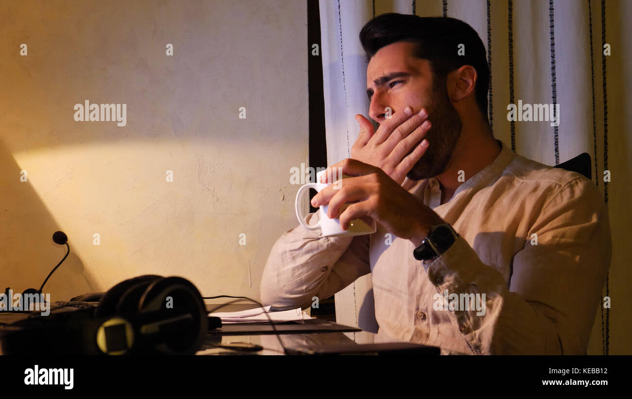 Home worker yawning at computer drinking coffee or tea - Stock Image