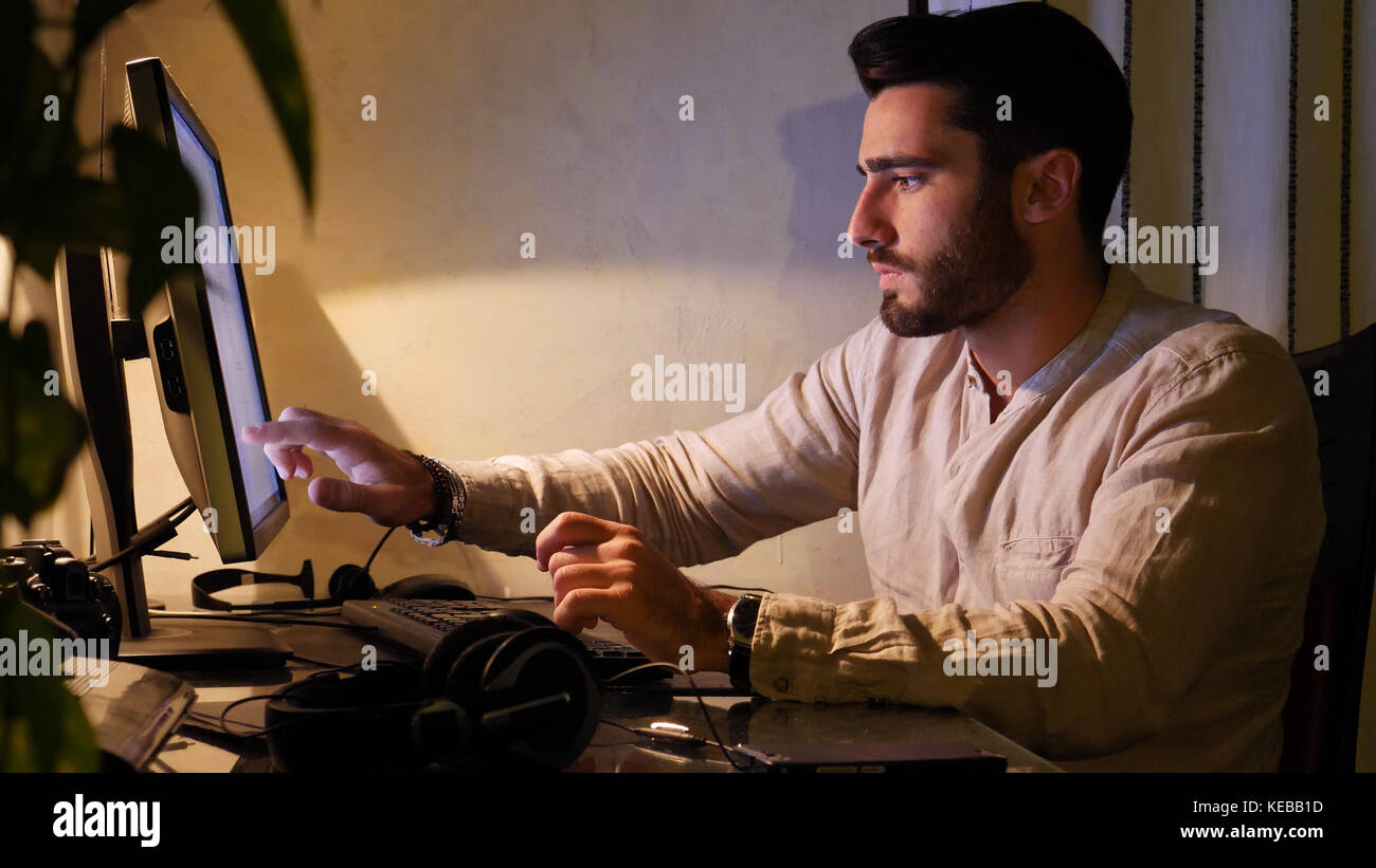 Home worker sitting at desk using touchscreen computer - Stock Image
