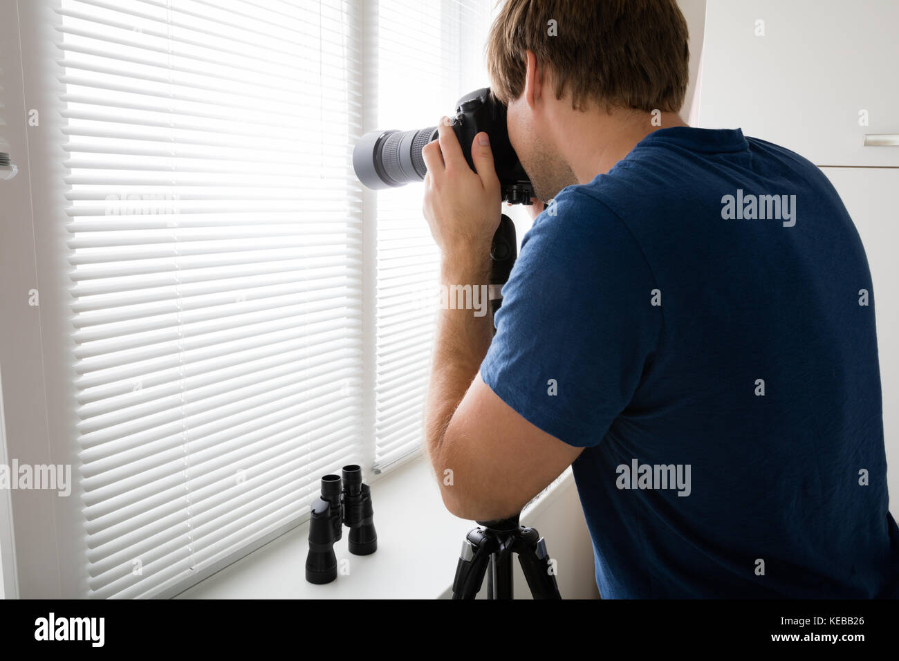 Private Detective Holding Camera Photographing Through Blinds At Home - Stock Image
