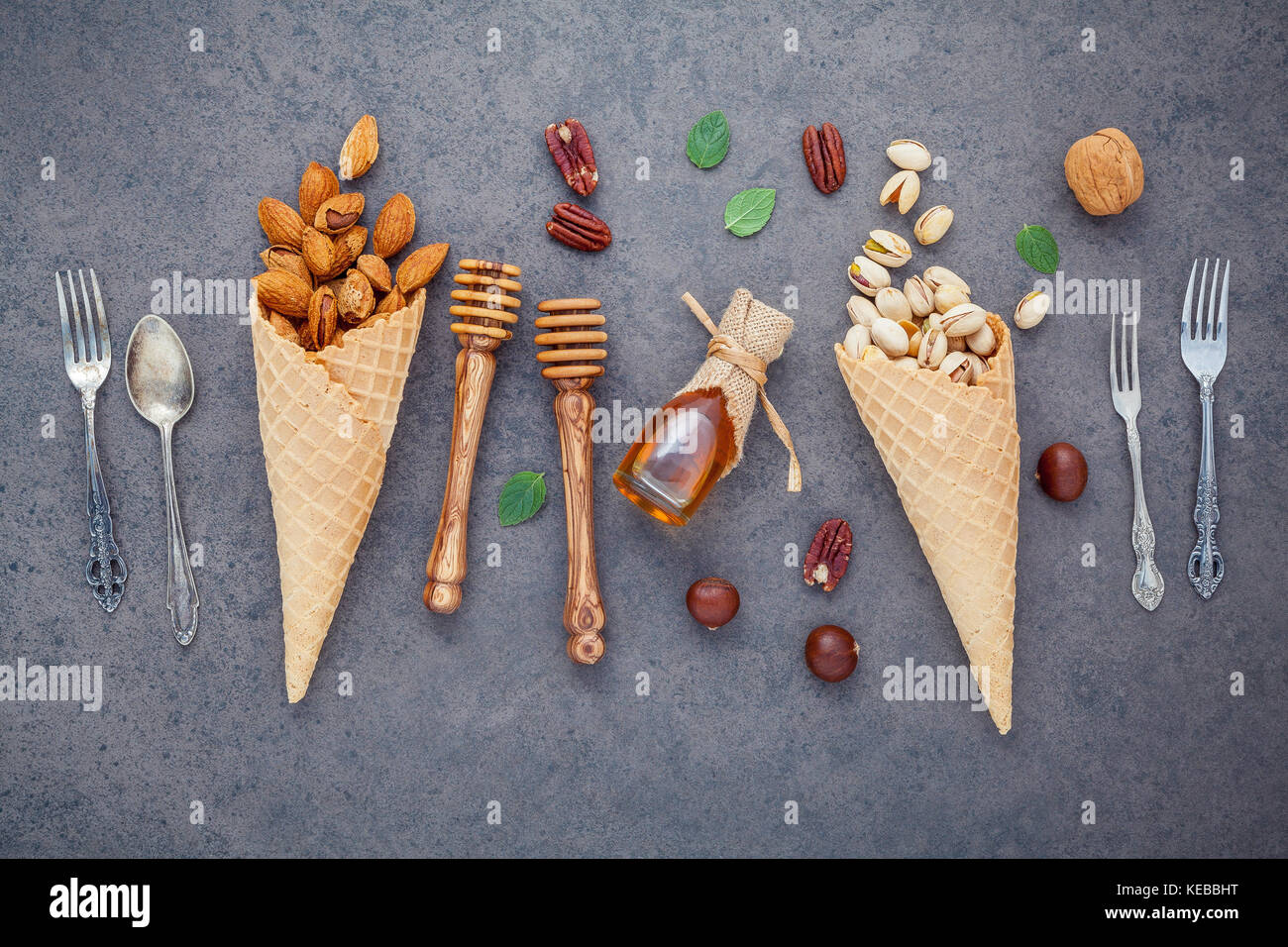 Concept for homemade various nuts ice cream. Mixed nuts in waffle cones ,metal utensils and honey dipper on  dark - Stock Image