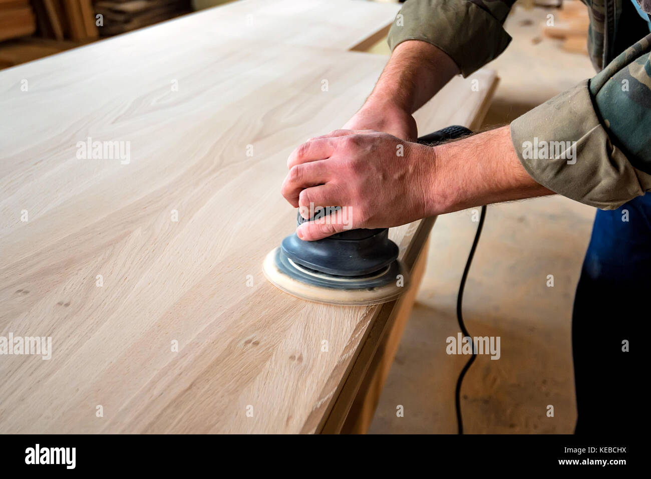 Man sanding wood with orbital sander in a workshop - Stock Image