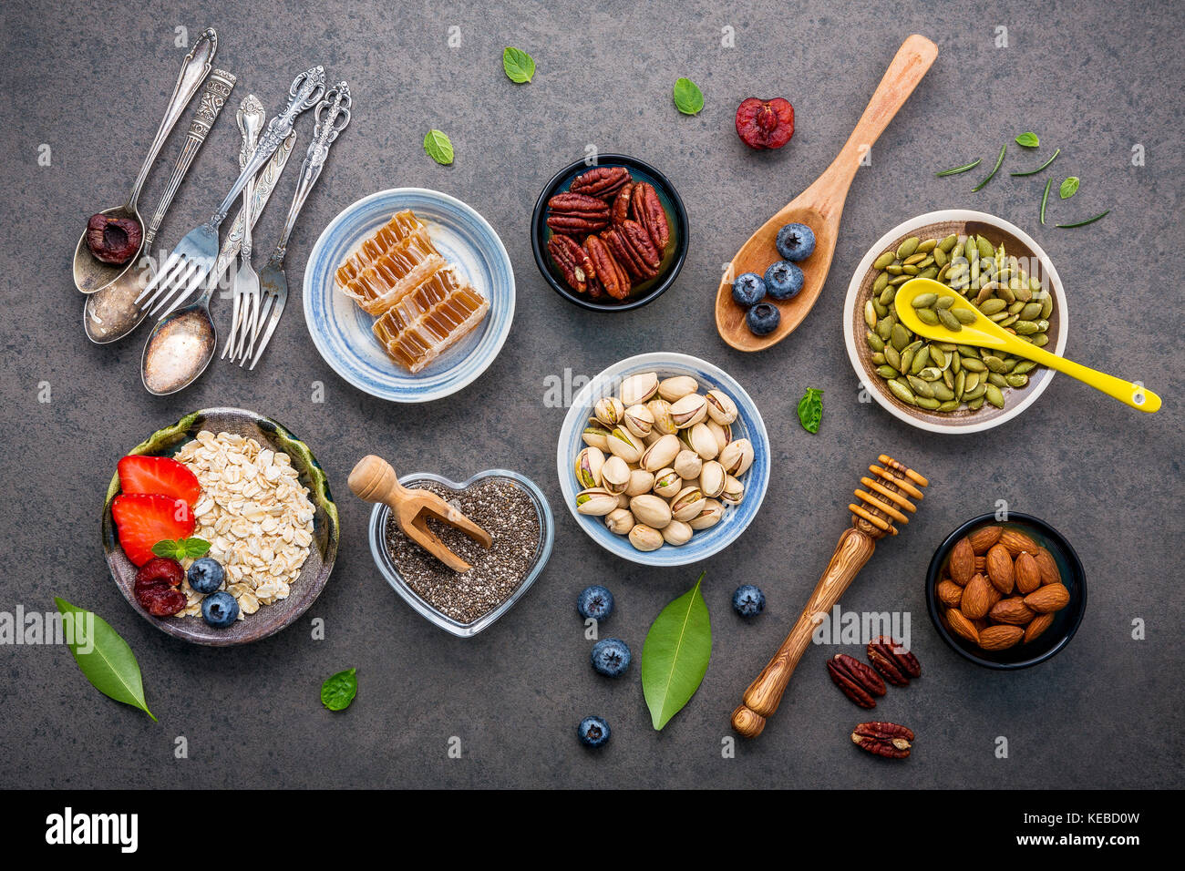 Ingredients for the healthy foods background Mixed nuts, honey, berries, fruits, blueberry, orange, almonds, oatmeal Stock Photo